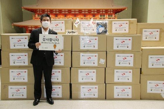 慶州市が送った防疫物品の前で「ありがとうございました」と書かれたカードを持って立つ仲川げん奈良市長。[写真 慶州市]