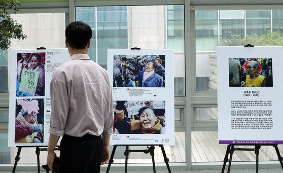 昨年8月、強制徴用-慰安婦問題関連の写真展示会がソウル汝矣島(ヨイド)国会議員会館で開かれた。市民が展示作品を観覧している。キム・ギョンロク記者