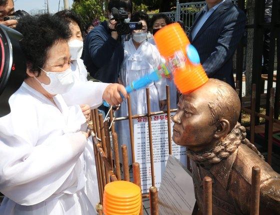 4月27日、光州地裁の前で犠牲者家族がハンマーで叩くパフォーマンスを行っている。