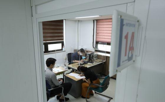 ある難民申請人が10日、ソウル木洞のソウル出入国外国人庁で、通訳者(左)の助けを受けて難民審査を受けている。キム・ソンニョン記者