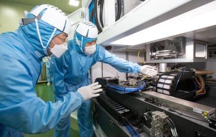 サムスン電子とEOテクニクスの職員が、2社が共同開発した半導体レーザー装置を一緒に見ている。[写真 サムスン電子]