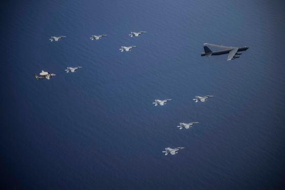 米本土から来た戦略爆撃機B-52Hストラトフォートレスが、米海軍の原子力空母「ニミッツ」(CVN68)のF-18スーパーホーネット戦闘機とE-2ホークアイの護衛の中で飛行している。[写真 米太平洋空軍]