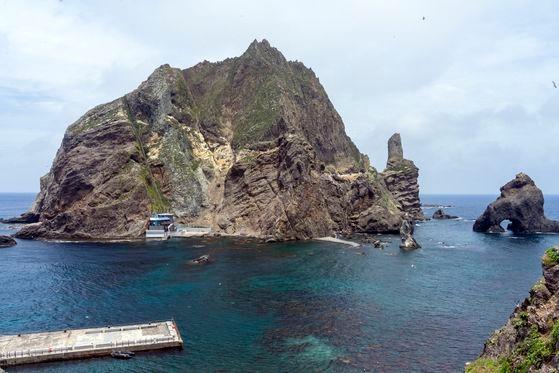 独島(ドクト、日本名・竹島)は東島と西島、そして約89の岩と暗礁で形成されている。東島の頂上から見下ろした船着き場と西島の様子。右側に見える岩は三兄弟窟岩だ。中央フォト