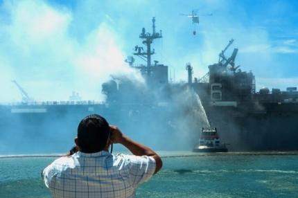 米国市民が米海軍の強襲揚陸艦であるボノム・リシャール(LHD6)の火災鎮圧作業を双眼鏡で見守っている。[写真 米海軍]