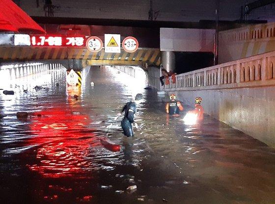 23日、大雨が降った釜山東区草梁洞釜山駅付近の第1地下車道に出動した消防隊員が救助作業を行っている。[写真 釜山消防災難本部]