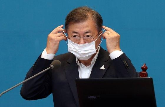 青瓦台首席秘書官補佐官会議が27日に開かれた。文在寅大統領が冒頭発言を終えた後マスクを着用している。[写真 青瓦台写真記者団]