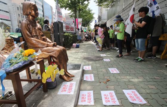 2019年8月14日、釜山の日本総領事館前の平和の少女像で開かれた日本軍慰安婦被害者をたてる日記念釜山第44回水曜デモに参加した釜山地域の市民社会団体会員らが少女像から労働者像まで手をつなぐパフォーマンスを展開している。