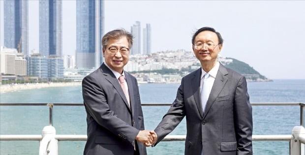 徐薫青瓦台国家安保室長(左)と楊潔チ中国共産党外交担当政治局員が22日、釜山ウェスティン朝鮮ホテルで会談を終えた後、ホテルの野外テラスで握手している。[写真 青瓦台写真記者団]