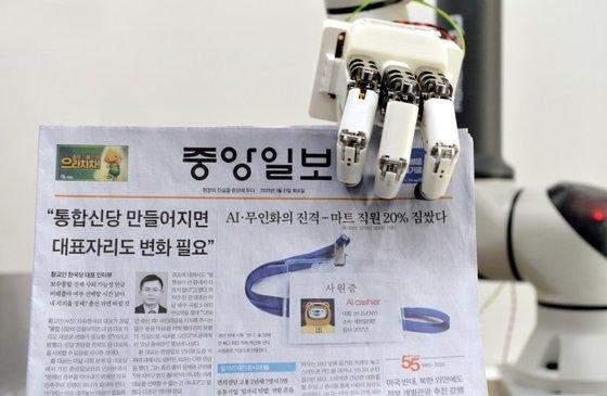 韓国機械研究院のト・ヒョンミン博士研究チームが1月に大田の韓国機械研究院先端生産装備研究本部ロボットメカトロニクス研究室で人間型ロボットの手で中央日報をつかんで見せている。[中央フォト]