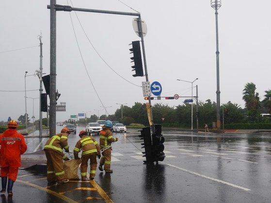 台風8号「バービー」の強風で26日午前、済州市連洞(ヨンドン)マリーナホテル前の交差点で信号が道路に倒れ、出動した消防隊員が安全対策を講じている。[ニューシス]