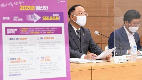 洪楠基(ホン・ナムギ)副首相兼企画財政部長官(左)が先月28日に開かれた2021年度予算案事前記者会見で発言している。右側は企画財政部のアン・ドゴル予算室長。[写真 企画財政部]