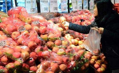 スーパーで食料品を買う女性。