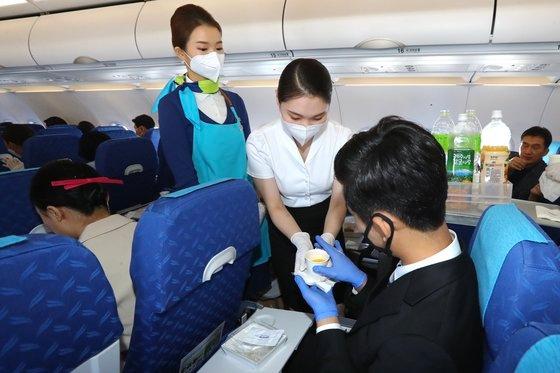 10日、韓国の航空会社で初めてエアプサンの目的地のない飛行体験プログラムに参加した慶北浦項市の威徳大学航空観光学科の学生80人余りが運行中のエア釜山の航空機内で実習体験をしている。ソン・ボングン記者