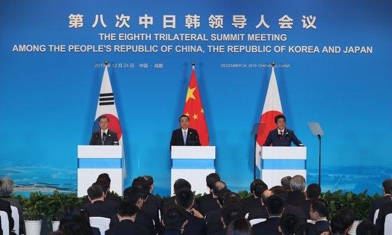 2019年12月、韓日中首脳会談を終えた後、(左から)韓国の文在寅(ムン・ジェイン)大統領、中国の李克強首相、安倍晋三前首相が四川省成都の世紀城国際会議センターで共同言論発表を行っている。[写真 青瓦台写真記者団]