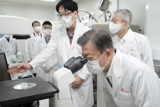 15日、京畿道城南のワクチン開発企業SKバイオサイエンスを訪問し、細胞培養室で顕微鏡を覗いている韓国の文在寅大統領。[写真 青瓦台写真記者団]
