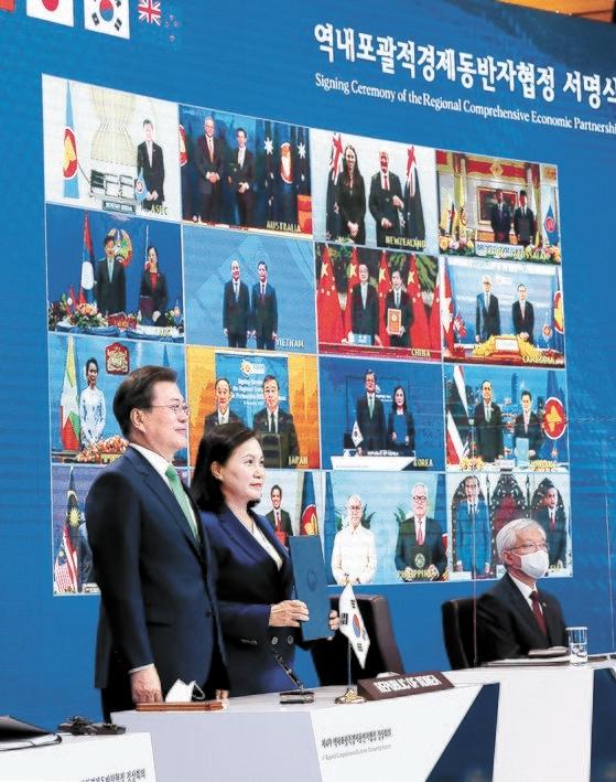 文大統領と兪明希(ユ・ミョンヒ)通商交渉本部長(右)が15日、青瓦台でテレビ会議で行われた「東アジア地域包括的経済連携(RCEP)」協定の書名式で記念撮影を行っている。[写真 青瓦台写真記者団]