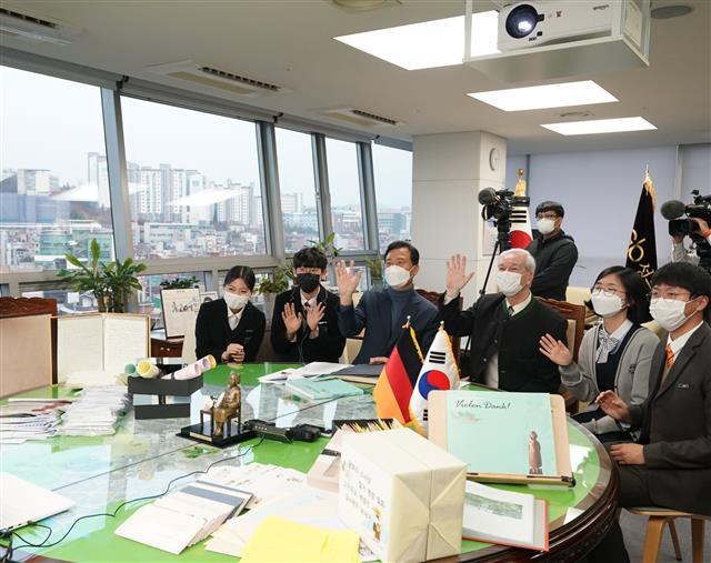 ソウル市城北区庁長と住民が手書きの手紙とともにドイツ現地とテレビ電話をしながら明るく笑っている。[写真 城北区提供]