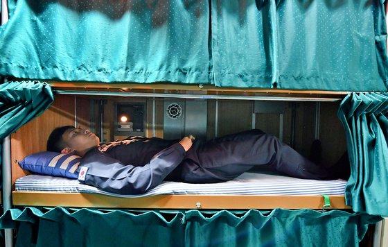 狭い潜水艦内部のベッドで乗組員が休んでいる。身長180センチ以上の人は足を完全に伸ばすことができない。 [写真=海軍]