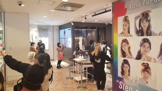22日、東京渋谷にある渋谷109に設置されたNiziU(ニジュー)のポップアップストアでファンが写真を撮っている。ユン・ソルヨン特派員