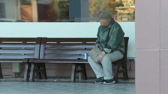 ベンチに座っている日本の高齢者。[中央フォト]