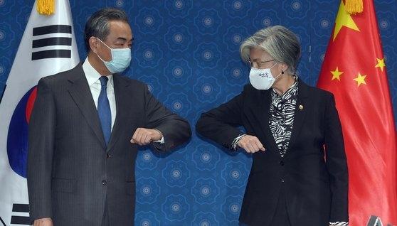 26日午前、韓国外交部を訪問した中国の王毅外交部長が康京和外交部長官と会談前に肘タッチで挨拶を交わしている。[写真 共同取材団]