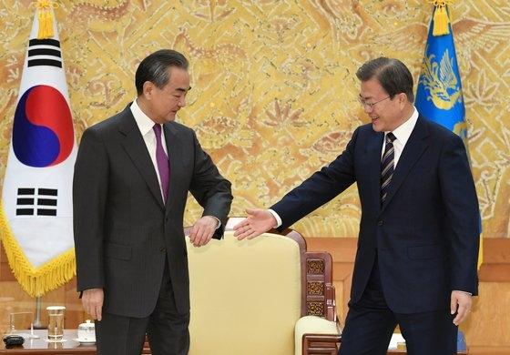 中国の王毅外交部長に対し、肘タッチの代わりに手を差し出した韓国の文在寅大統領。[写真 青瓦台写真記者団]