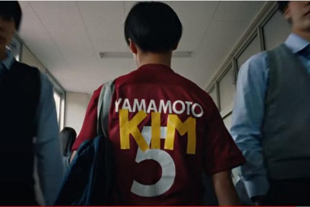 在日朝鮮人サッカー選手が日本式の名前「山本(YAMAMOTO)」の上に「キム(KIM)」という名前を重ねたユニホームを着て歩いている。(写真YouTube画面キャプチャー)