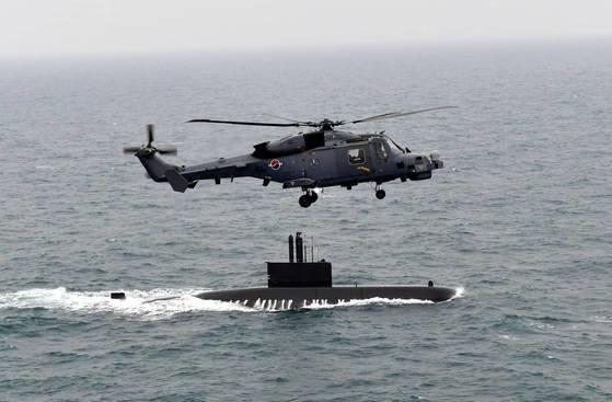 海上作戦ヘリコプター「ワイルドキャット」(AW-159)が海軍潜水艦と海上作戦をしている。 [海軍提供]