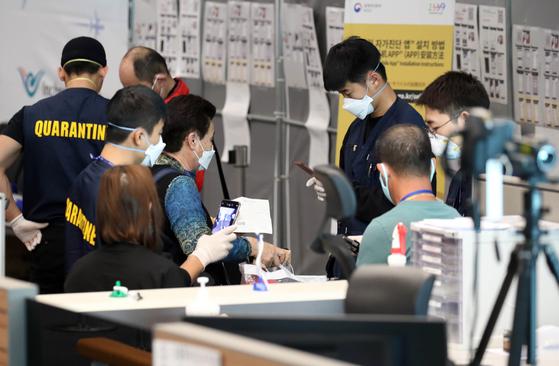 韓日両国間の相互ノービザ入国が中断した2020年3月9日、仁川国際空港第2ターミナルで日本発旅客機に乗って到着した乗客が検疫と連絡先確認など特別入国手続きを踏んでいる。 キム・ソンリョン記者