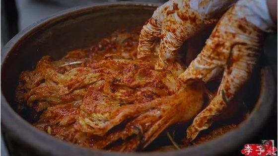 中国ユーチューバー、李子チーが白菜キムチを漬けている様子。[写真 YouTubeキャプチャー]