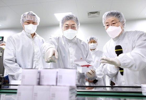 文在寅(ムン・ジェイン)大統領が先月20日午前、慶北安東市のSKバイオサイエンスを訪問して新型肺炎ワクチンの生産施設を見学し、イ・サンギュン工場長の説明を聞いている、左側は崔泰源(チェ・テウォン)SK会長。[中央フォト]