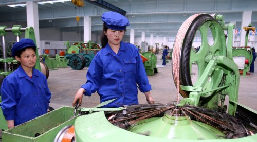 北朝鮮の女性労働者が、電力ケーブル生産設備を調べている。[中央フォト]