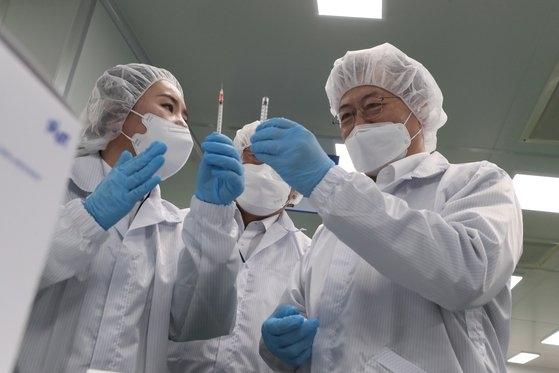 文在寅大統領が18日午後、全北群山市(チョンブク・クンサンシ)の新型肺炎ワクチン接種用の最小残留型注射器(LDS)の生産現場であるプンリムファーマテックを視察し、プンリムファーマテックのチョ・ミヒ副社長からワクチン注射器の生産ラインに関する説明を聞いている。[写真 青瓦台写真記者団]