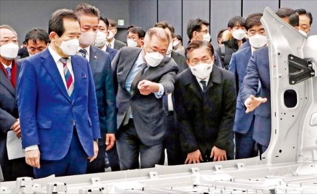 鄭義宣(チョン・ウィソン)現代自動車グループ会長(真ん中)が18日、京畿道華城市の現代車ナムヤン技術研究所で、丁世均(チョン・セギュン)首相(左)、成允模(ソン・ユンモ)産業通商資源部長官(右)に電気自動車専用プラットホーム(E-GMP)について説明している。丁首相はこの日、ナムヤン技術研究所で国政懸案点検調整会議を開いた後、鄭会長と共にE-GMPが適用された最初の電気自動車「アイオニック5」と燃料電池トラック「エクシエント」に試乗した。丁首相は「電気自動車生態系が完成するよう関係部処が後続対策を進めてほしい」と指示した。 キム・ヨンウ記者