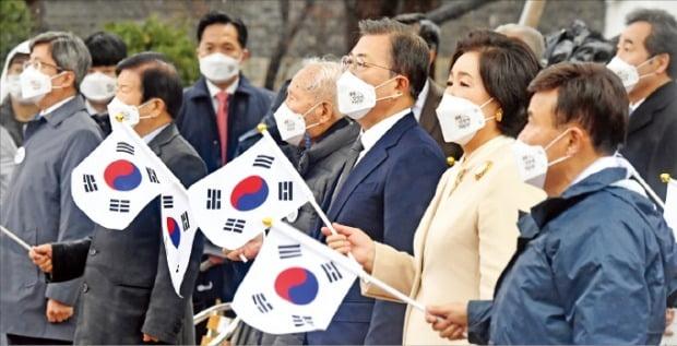 <太極旗を振る文大統領>韓国の文在寅(ムン・ジェイン)大統領と金正淑(キム・ジョンスク)夫人が1日、ソウル鍾路(チョンノ)タプコル公園で開かれた三一節記念式典で太極旗を手に三一節の歌を歌っている。ホ・ムンチャン記者
