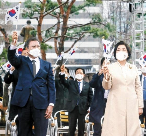 韓国の文在寅(ムン・ジェイン)大統領と金正淑(キム・ジョンスク)夫人が1日午前、ソウル鍾路区(チョンノグ)のタプコル公園で開かれた第102周年三一節記念式典に出席して万歳三唱をした後、大極旗を振っている。[写真 青瓦台写真記者団]