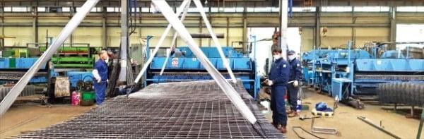 急騰した国際原材料価格と海上運賃が中小製造現場に大きな打撃を与えている。忠清南道地域の金網メーカーで従業員が品質確認作業をしている。[写真 韓国経済DB]