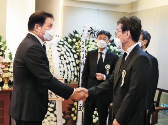 崔泰源(チェ・テウォン)会長(左)が27日、故辛春浩(シン・チュンホ)農心会長の葬儀場を訪れた後、三男の辛東益(シン・ドンイク)メガマート副会長とあいさつしている。 [写真 農心]