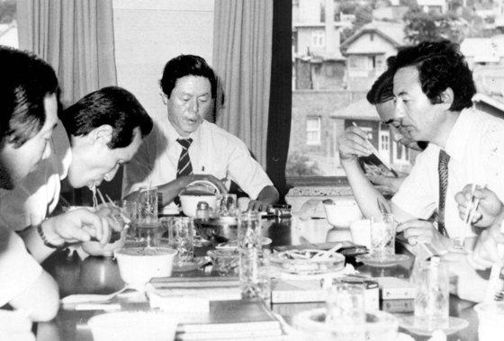 農心(ノンシム)の役職員と、1982年、カップラーメンの新商品を味わっているの辛春浩(シン・チュンホ)会長(中央)。辛会長は1965年ロッテ工業を創業し、ラーメン事業に参入した。[写真 農心]