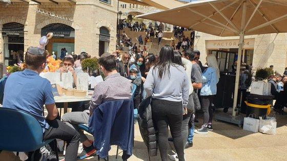 イスラエルの飲食店の前に置かれた野外テーブル席は人々で一杯で、店の前には長い列ができている。[写真 イスラエル海外同胞 イ・ガングンさん]
