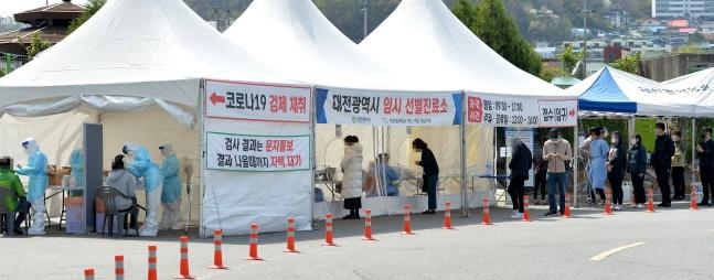 新型コロナウイルス感染が拡大する中、6日、大田(テジョン)ハンバッ体育館前の新型コロナ選別診療所を訪れた市民が検査を受けるため列に並んでいる。 中央フォト
