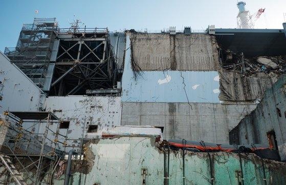 2011年の東日本大震災当時の爆発事故で外壁が崩れた福島第1原発。 [中央フォト]