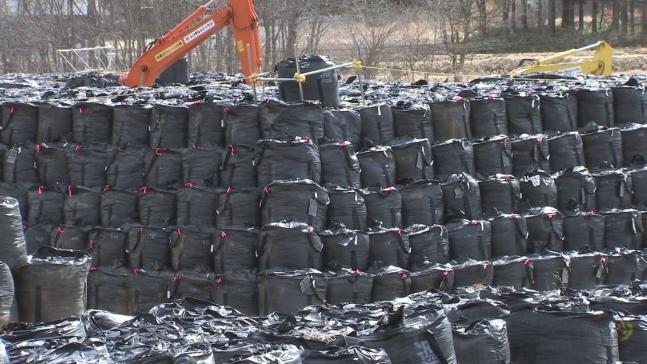 福島県飯舘村では除去土壌が入った袋が積まれている。 中央フォト