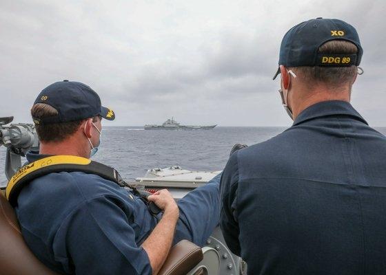 米第7艦隊所属のイージス艦「マスティン」の艦長(左)と副艦長(右)が、海上訓練中の中国空母「遼寧」を両足を欄干にのせたまま監視している。 [写真=米海軍]