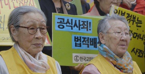 21日、慰安婦被害者の金福童さんなど20人が日本政府を相手取って提起した損害賠償請求訴訟の宣告が行われる。写真は慰安婦被害者を題材にしたドキュメンタリー映画『アポロジー』の金福童さん、吉元玉(キル・ウォノク)さんの姿。[写真 映画会社グラム]