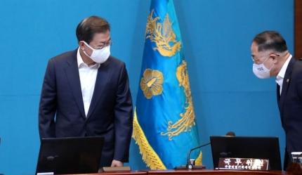 閣僚会議で文在寅大統領(左)と洪楠基経済副首相があいさつを交わしている。[写真 青瓦台写真記者団]