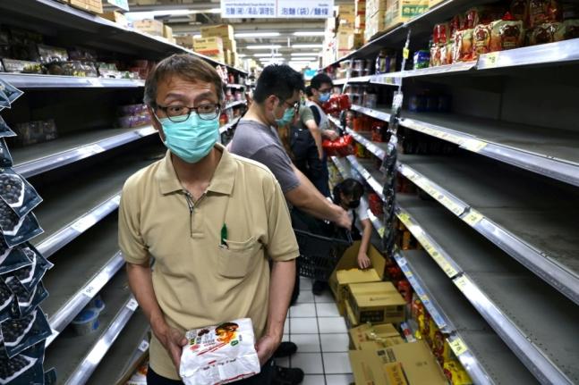 買い占めで空っぽになった台北市内の商店の陳列棚。[写真 ロイター]
