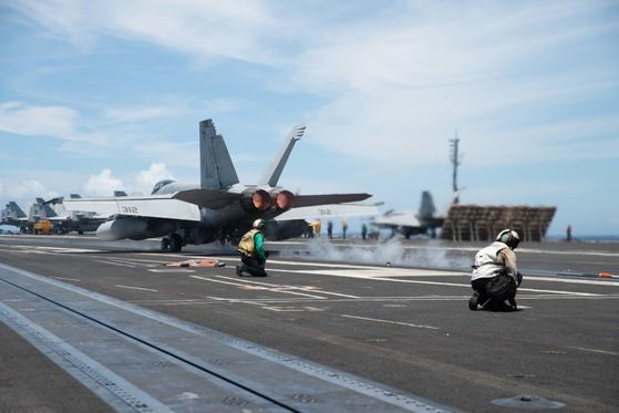 日本海上自衛隊と合同訓練に参加した米国海軍の原子力空母艦「ロナルド・レーガン」(CVN 76)の甲板からF/A-18Fスーパーホーネット戦闘機が離陸の準備をしている。[写真 米国海軍]