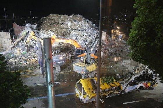 9日午後、光州市東区鶴洞(クァンジュシ・トング・ハクドン)の建物崩壊現場の路上で建物残骸の撤去作業が行われた。下敷きになっていた市内バスが押しつぶされた状態で移送を待っている。フリーランサー チャン・ジョンピル