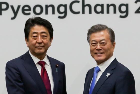 文在寅大統領が2018年に平昌五輪開幕式参加のため訪韓した当時の安倍晋三首相と握手している。[写真 青瓦台写真記者団]